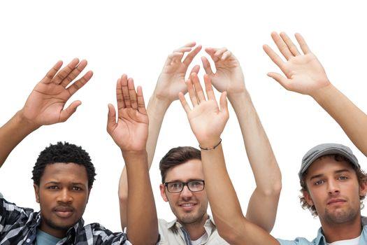 Portrait of three young men raising hands