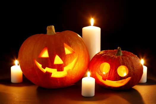 Halloween pumpkins surrounded with candles isolated on black background