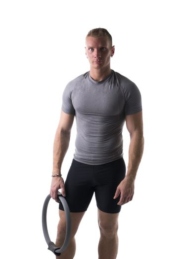 Young muscular man relaxed with Pilates ring in hand, isolated on white