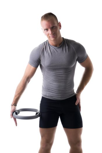 Young muscular man exercising with Pilates ring against thigh, isolated on white