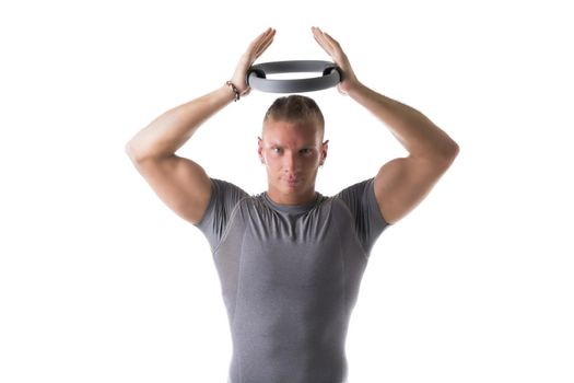 Young muscular man exercising with Pilates ring above his head, isolated on white