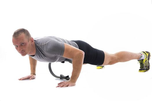 Young blond muscular man exercising on the floor with Pilates ring isolated on white