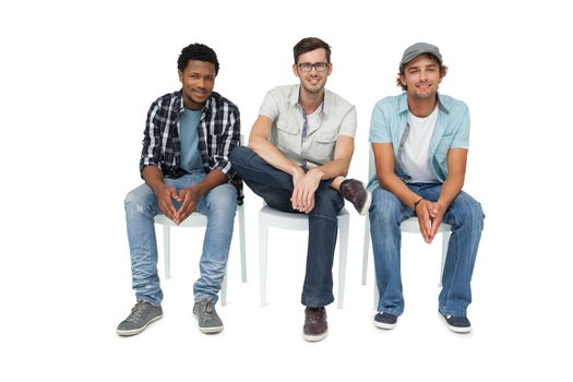 Portrait of three cool young men sitting on chairs
