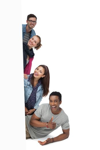 Portrait of four happy young friends with blank board