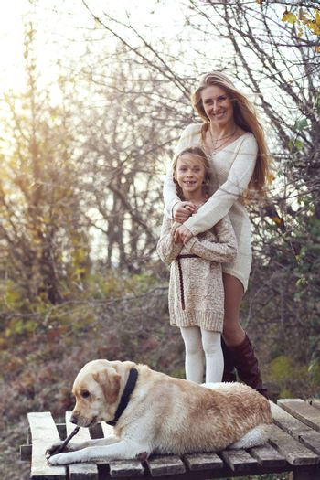 Mother with her 7 years old daughter walking with dog in autumn