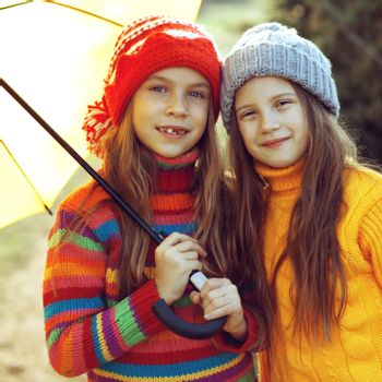 Cute 7 years old girls wearing knitted winter sweaters walking outdoors in autumn
