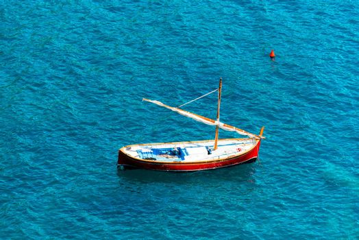 Typical Italian small wooden sailing boat, red, white and blue, between the waves of the sea. Liguria, Italy