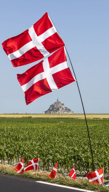 Image of the famous Mont Saint Michel Monastery, partially framed by Norwegian flags, on the roadside during the stage 11 of the edition 100 of Le Tour de France 2013, a time trial between Avranches and Mont Saint Michel.
