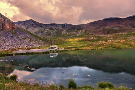 Colorful sunset over the Lake Essaupres located at 2306 m altitude near one of the highest asphalted road in Europe which lead to Col de la Bonette (2715 m) in Alpes-de-Haute-Provence, south of France.
