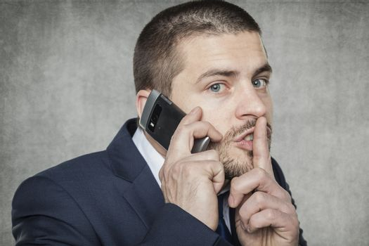 businessman talking on the phone and asks for silence
