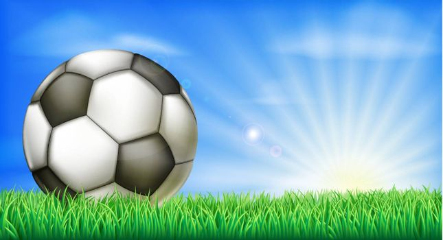 A soccer football in a green grass field pitch with sun rise.
