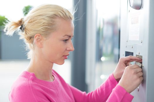Woman inserting coin in the vending machine.
