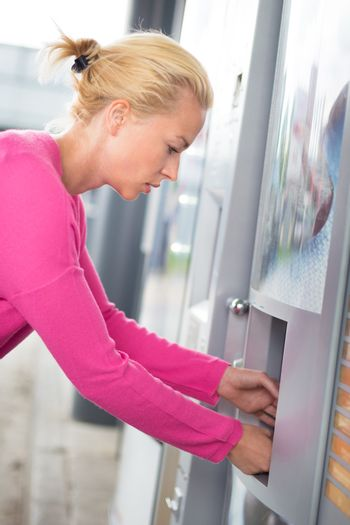 Lady collecting product from vending machine.