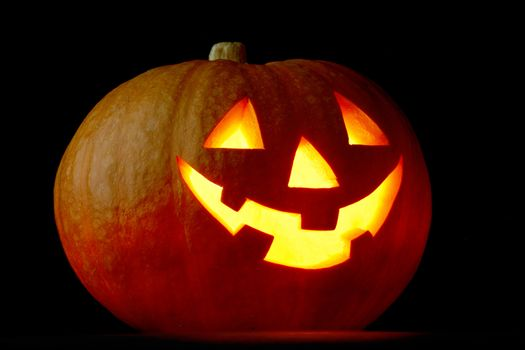 Illuminated cute glowing halloween pumpkin on black background
