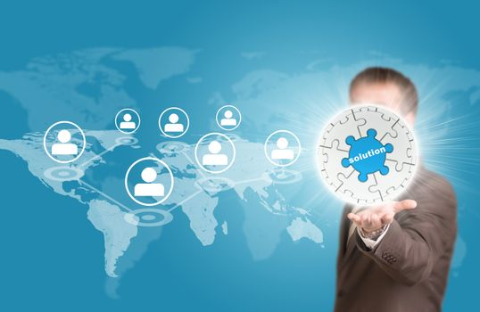 Business man hold puzzle sphere with business label. World map and network as backdrop