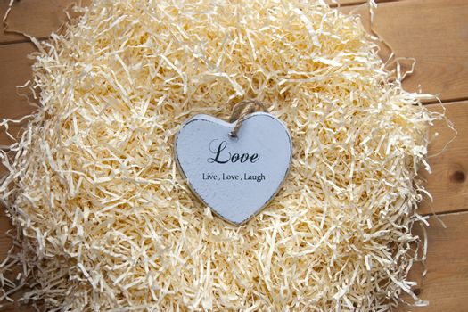 single grey wooden love heart in a love nest made of straw inscribed  love, live and laugh