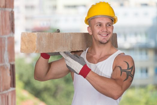 Handsome Man Carrying Wood Planks