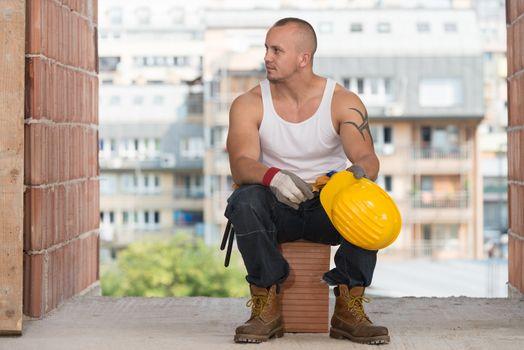 Tired Builder Resting On Brick