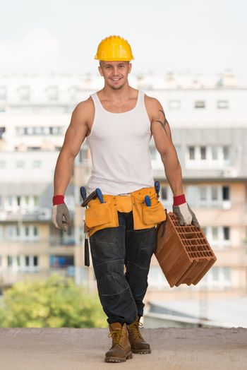 Young Handsome Builder With Brick