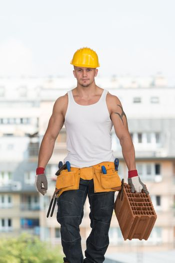 Construction Worker At Work With Brick