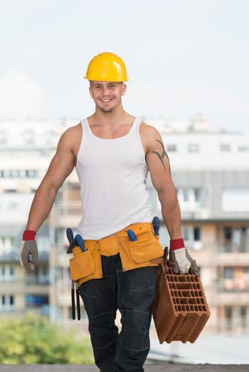 Construction Worker Carrying Brick