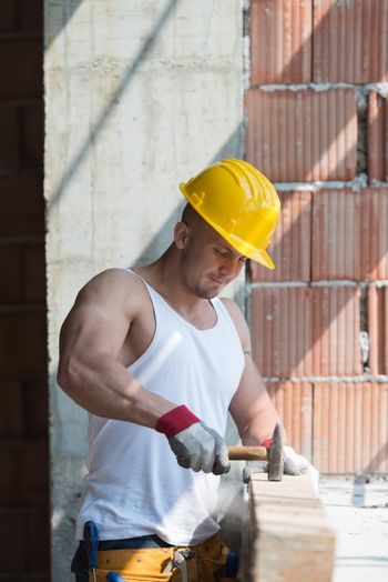 Builder Working With Hammer And Nail