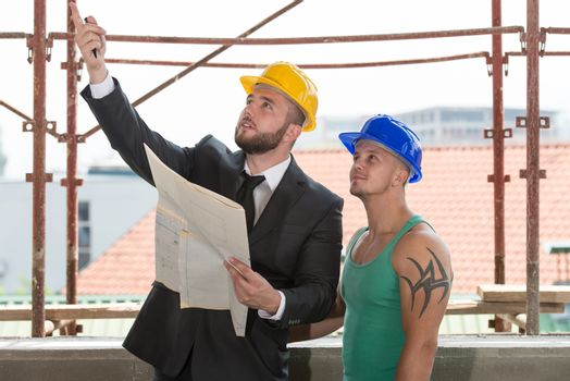 Businessman Showing Industrial Worker At Construction