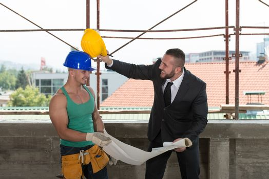 Businessman And Industrial Worker Playing Around