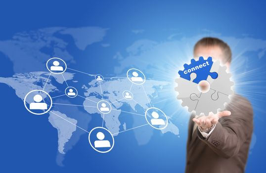 Business man hold gear in hand. World map with contact icons as backdrop