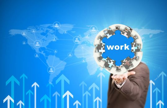 Business man hold puzzle sphere with Work label. World map, contact icons and arrows as backdrop