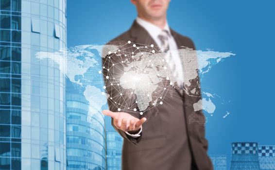 Business man hold world map and wire-frame sphere in hand. Building as backdrop