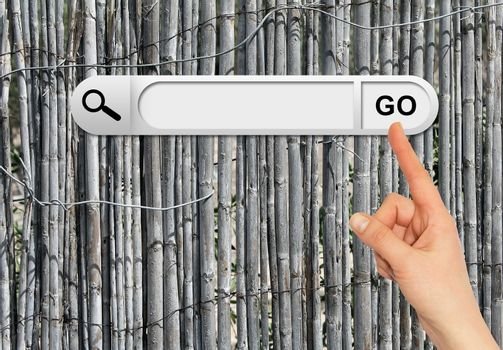 Human hand indicates the search bar in browser. Old gray wooden fence on background