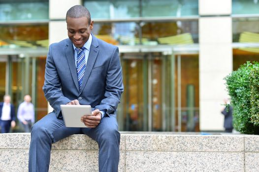 Relaxed businessman using his tablet pc