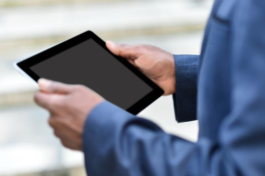 Businessman holding digital tablet outdoors