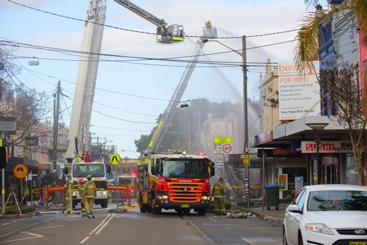 Firemen douse flames after explosion at a convenience store in Rozelle