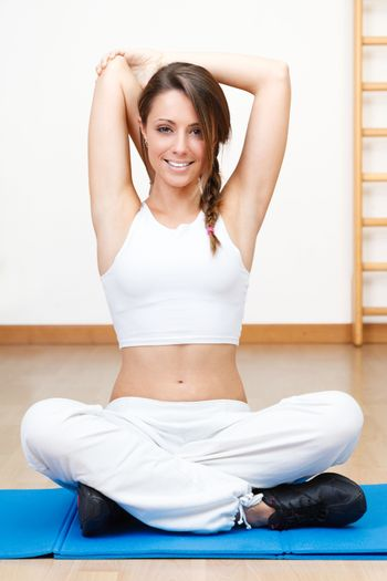 woman stretching the muscles of her in yoga class