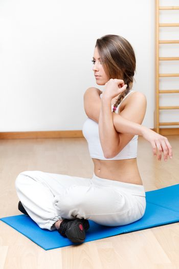 beautiful young woman stretching the muscles of her in yoga clas