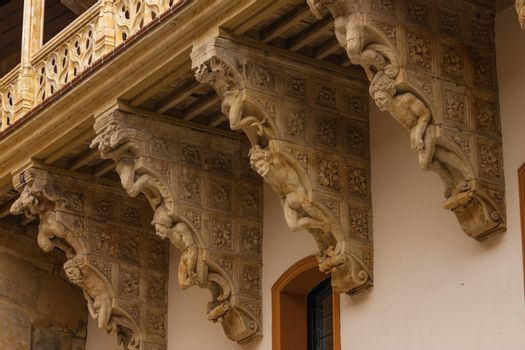 original corbel decoration in La Salina Palace courtyard with twisted carved bodies in Salamanca Spain