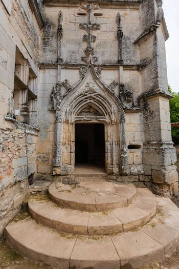 Main entrance door in renaissance style of the ruined castle of L��Herm in the french region of Dordogne