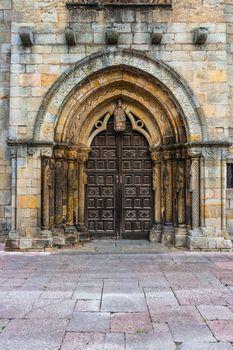 Beautiful Romanesque main entrance in the church of Santa Maria de la Oliva in the town of Villaviciosa Spain