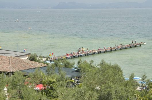 People sunbathing on wooden pier  in Sirmione, located in the lake Garda, Italy