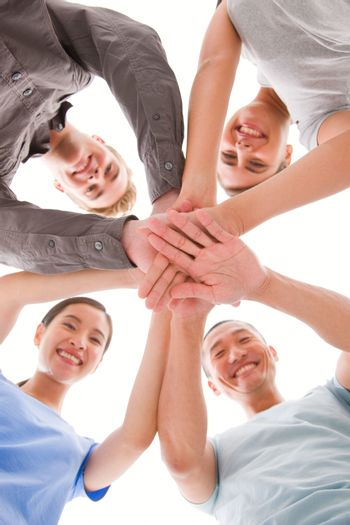 Happy businesspeople placing their hands top of each other