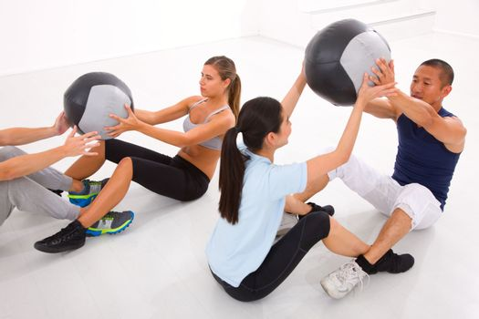 Diverse group of people exercising with pilates in gym