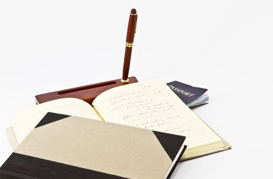 Passport placed beneath open journal with desk pen and another book.