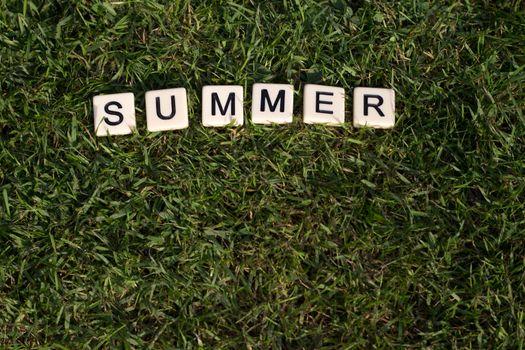 Summer written in tiles on green grass