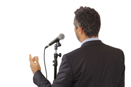 Rear view of a male public speaker speaking at the microphone, pointing, isolated with white background, symbol of leadership and international conferences