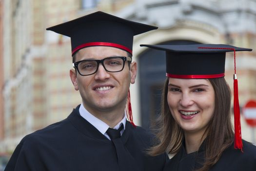 Outdoor portrait of a young couple of students in the graduation day near the university building.
