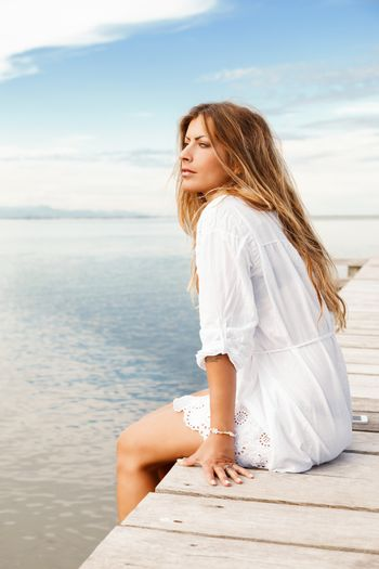 Young woman in white clothes on a pier