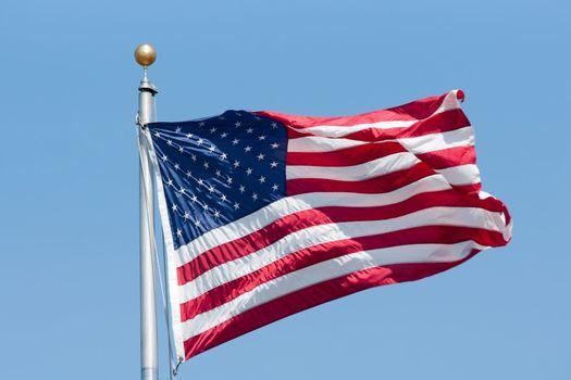 American flag fluttering on the blue sky