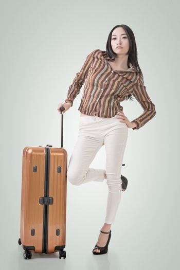 Modern Asian woman stand with a luggage, full length portrait on white background.